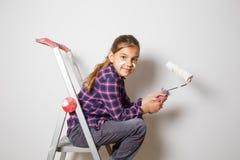 Muchacha adolescente en escalera del edificio usando un cepillo para pintar en el w Foto de archivo