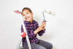Muchacha adolescente en escalera del edificio usando un cepillo para pintar en la pared blanca Fotos de archivo libres de regalías