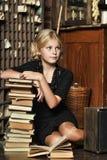 Muchacha adolescente en estilo retro con una pila de libros Fotos de archivo libres de regalías
