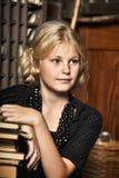 Muchacha adolescente en estilo retro con una pila de libros Imagenes de archivo