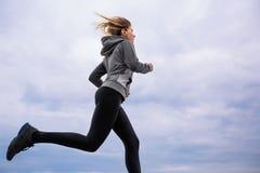 Muchacha adolescente en funcionamientos de la ropa de deportes contra el cielo nublado fotos de archivo