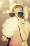 Muchacha adolescente en gafas de sol que come el caramelo de algodón en la calle de la ciudad Imagenes de archivo