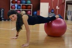 Muchacha adolescente en gimnasio en bola del poder Imágenes de archivo libres de regalías
