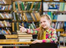 Muchacha adolescente en la biblioteca que muestra el pulgar para arriba Foto de archivo