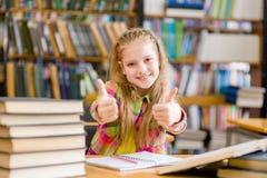 Muchacha adolescente en la biblioteca que muestra los pulgares para arriba Imagenes de archivo