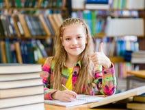 Muchacha adolescente en la biblioteca que muestra los pulgares para arriba Fotos de archivo libres de regalías