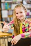 Muchacha adolescente en la biblioteca que muestra los pulgares para arriba Fotos de archivo