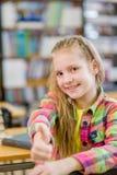Muchacha adolescente en la biblioteca que muestra los pulgares para arriba Fotografía de archivo libre de regalías