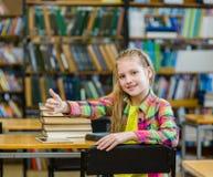 Muchacha adolescente en la biblioteca que muestra los pulgares para arriba Imágenes de archivo libres de regalías