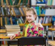 Muchacha adolescente en la biblioteca que muestra los pulgares para arriba Fotografía de archivo