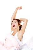 Muchacha adolescente en la cama que bosteza. Foto de archivo
