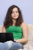 Muchacha adolescente en la cama que mira en su computadora portátil Fotos de archivo libres de regalías