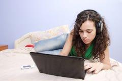Muchacha adolescente en la cama que mira en su computadora portátil Fotografía de archivo libre de regalías