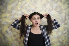 Muchacha adolescente en la camisa de tela escocesa que tira del pelo Imagenes de archivo