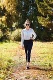 Muchacha adolescente en la camisa y las gafas de sol blancas al aire libre en verano fotografía de archivo libre de regalías