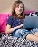 Muchacha adolescente en la computadora portátil Foto de archivo libre de regalías
