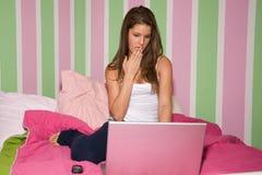 Muchacha adolescente en la computadora portátil Imágenes de archivo libres de regalías