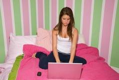 Muchacha adolescente en el ordenador portátil imagen de archivo