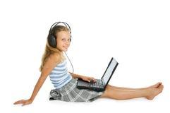 Muchacha adolescente en la computadora portátil con los auriculares Imagenes de archivo