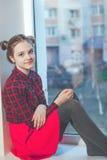 Muchacha adolescente en la falda roja que se sienta en travesaño de la ventana Imágenes de archivo libres de regalías