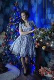 Muchacha adolescente en la Navidad en el árbol de navidad hermoso g Fotos de archivo libres de regalías