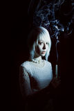 Muchacha adolescente en la oscuridad con una vela, miedo en ella Imágenes de archivo libres de regalías