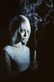 Muchacha adolescente en la oscuridad con una vela, miedo en ella Fotos de archivo