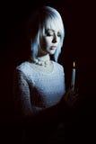 Muchacha adolescente en la oscuridad con una vela, miedo en ella Imagenes de archivo