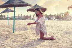 Muchacha adolescente en la playa que juega con la arena Imagenes de archivo