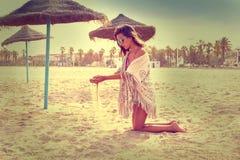 Muchacha adolescente en la playa que juega con la arena Fotos de archivo