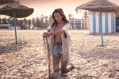 Muchacha adolescente en la playa que juega con la arena Imagen de archivo