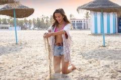 Muchacha adolescente en la playa que juega con la arena Imágenes de archivo libres de regalías
