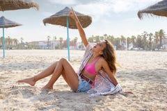 Muchacha adolescente en la playa que señala el cielo del finger Imagen de archivo libre de regalías