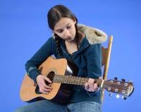 Muchacha adolescente en la silla que toca la guitarra Foto de archivo libre de regalías