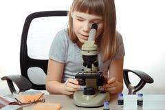 Muchacha adolescente en laboratorio de la escuela Investigador que trabaja con el microscopio Imagen de archivo libre de regalías