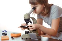 Muchacha adolescente en laboratorio de la escuela Investigador que trabaja con el microscopio Fotografía de archivo libre de regalías