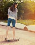 Muchacha adolescente en longboard en la calle Imagenes de archivo