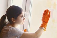 Muchacha adolescente en los guantes de goma anaranjados que limpian la ventana Foto de archivo