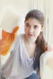 Muchacha adolescente en los guantes de goma anaranjados que limpian la ventana Fotografía de archivo libre de regalías