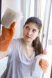 Muchacha adolescente en los guantes de goma anaranjados que limpian la ventana Imágenes de archivo libres de regalías