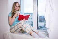 Muchacha adolescente en los pijamas que se sientan por la ventana con el libro y la taza de Imagenes de archivo