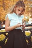 Muchacha adolescente en parque del otoño con el teléfono móvil Fotografía de archivo