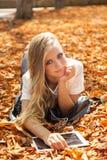 Muchacha adolescente en parque del otoño con PC Foto de archivo libre de regalías