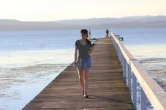 Muchacha adolescente en pasarela de madera en el lago Fotos de archivo libres de regalías
