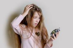 Muchacha adolescente en pijamas con el cloock de la alarma Fotos de archivo libres de regalías
