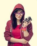 Muchacha adolescente en rojo con la cámara en el fondo blanco. Imagen de archivo