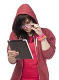 Muchacha adolescente en rojo con la tableta en el fondo blanco. Imágenes de archivo libres de regalías