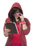 Muchacha adolescente en rojo con la tableta en el fondo blanco. Foto de archivo