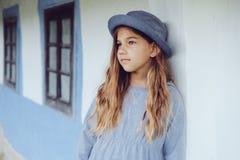 Muchacha adolescente en ropa casual y sombrero azul cerca por la casa del pueblo Imagen de archivo