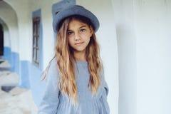 Muchacha adolescente en ropa casual y sombrero azul cerca por la casa del pueblo Imagenes de archivo